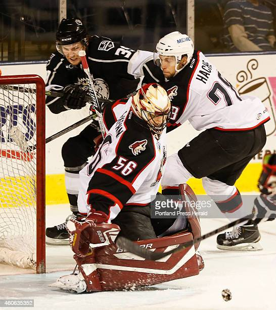 Portland Pirates goalie Mike McKenna watches a puck slide across the crease as teammate Justin Hache tries to keep MonarchsJustin Auger away from the...