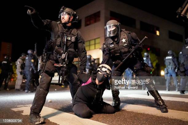 Portland police and Oregon State Patrol officers work together to arrest a protester in front of the Portland Police Bureau North Precinct on the...