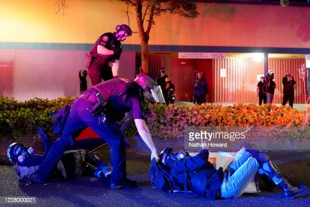 Portland police and Oregon State Patrol troopers work together to arrest two protesters in front of the Portland Police Bureau North Precinct on the...