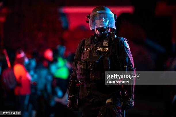 Portland police are seen in riot gear during a standoff with protesters in Portland, Oregon on August 16, 2020. Protests have continued for the 80th...