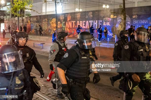 Portland police disperse a crowd of protesters past a mural of George Floyd and Breonna Taylor on September 26 2020 in Portland Oregon Oregon...