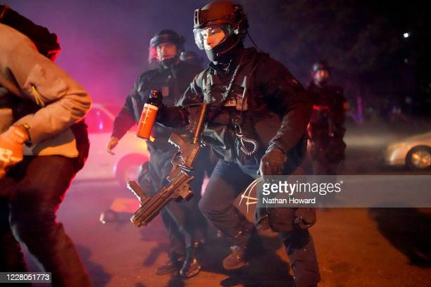 Portland police officer carries a can of pepper spray through smoke during a crowd dispersal on August 14, 2020 in Portland, Oregon. The Portland...