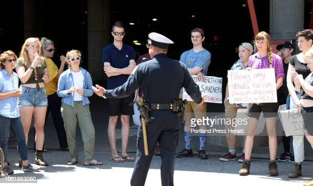 Portland police officer encourages protesters to leave the entrance to the garage at 100 Middle St where Attorney General Jeff Sessions was speaking...