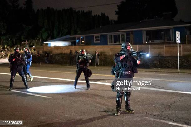 Portland police officer points a less lethal weapon at antipolice protesters near the east police precinct a day after political violence left one...