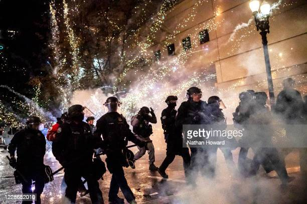 Portland police react as a firecracker explodes behind their police line on September 23 2020 in Portland United States Violent protests erupted...