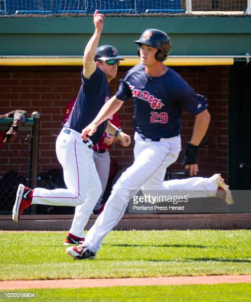 Portland Sea Dogs third base coach Darren Fenster waves baserunner Bobby Dalbec home as Luke Tendlers fourth inning double drives in two against the...