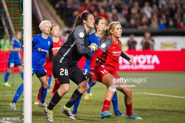 Portland Thorns midfielder Allie Long and Seattle Reign goal keeper Haley Kopmeyer jokey for position during a corner in the 22 tie between Portland...