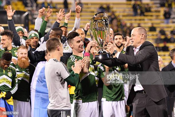 Portland Timbers owner Merritt Paulson hands the MLS Cup trophy to Liam Ridgewell of the Portland Timbers on December 6 2015 at MAPFRE Stadium in...
