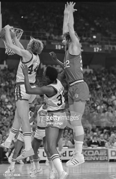 Portland Trail Blazers center Bill Walton and Denver Nuggets center Dan Issel sandwich Nugget forward Paul Silas on a rebound attempt during an NBA...