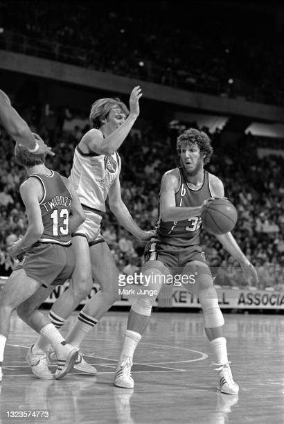 Portland Trail Blazers center Bill Walton holds the ball with one hand while being guarded by Denver Nuggets center Dan Issel during an NBA...