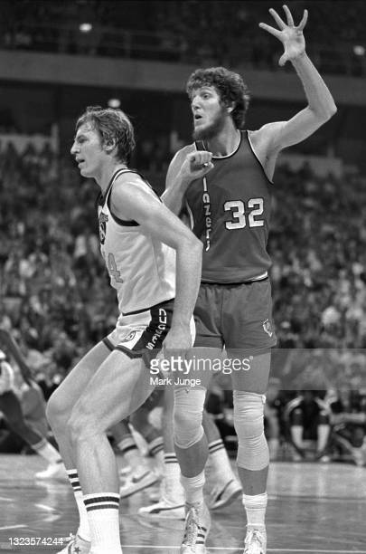 Portland Trail Blazers center Bill Walton looks for a pass over Denver Nuggets center Dan Issel during an NBA basketball game at McNichols Arena on...