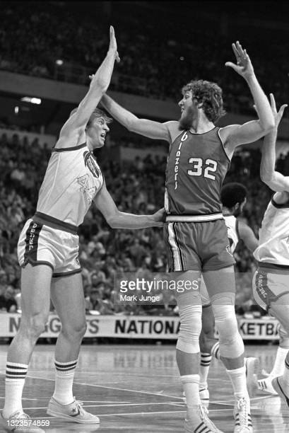Portland Trail Blazers center Bill Walton looks to receive a pass while being guarded by Denver Nuggets center Dan Issel during an NBA basketball...