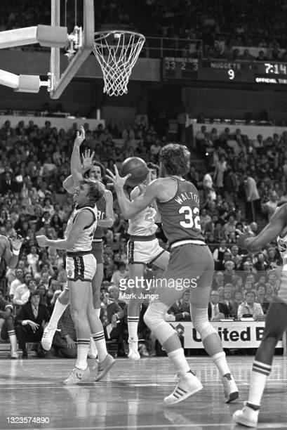 Portland Trail Blazers center Bill Walton receives a pass from teammate Bob Gross over the head of Denver Nuggets center Dan Issel during an NBA...