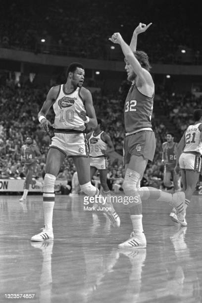 Portland Trail Blazers center Bill Walton signals a play as he runs downcourt next to Denver Nuggets center Marvin Webster during an NBA basketball...
