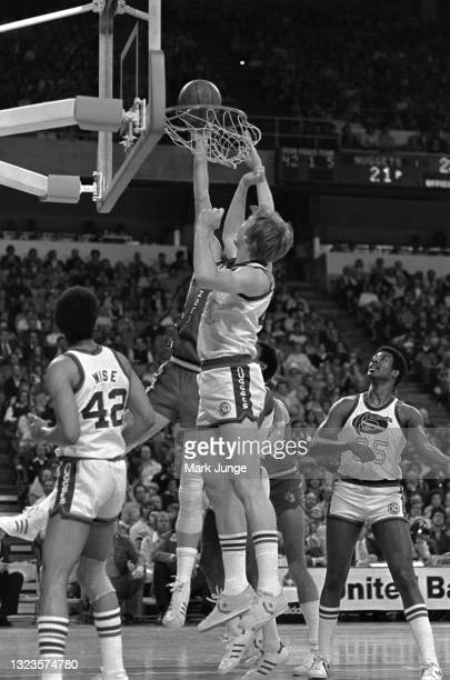 Portland Trail Blazers center Bill Walton throws the ball through the basket in the face of Denver Nuggets center Dan Issel during an NBA basketball...