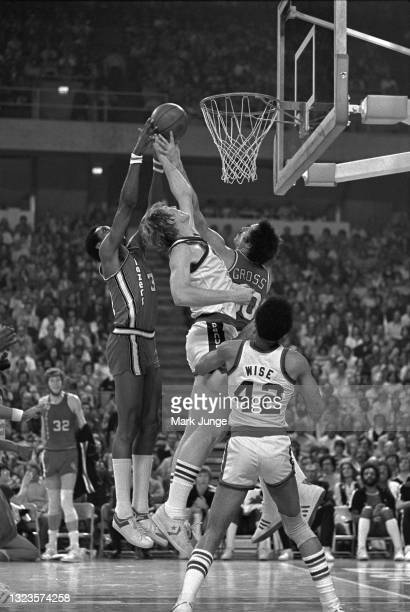 Portland Trail Blazers center Robin Jones and Bob Gross contest a rebound with Denver Nuggets center Dan Issel during an NBA basketball game at...