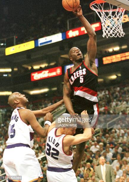 Portland Trail Blazers forward Jermaine O'Neal soars above Phoenix Suns forward Danny Manning and guard Jason Kidd during the first quarter of their...