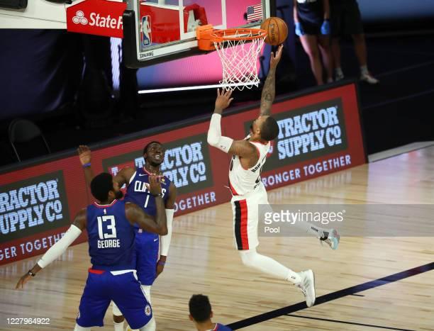 Portland Trail Blazers guard Damian Lillard shoots past LA Clippers guard Paul George and guard Reggie Jackson during the first half in an NBA...