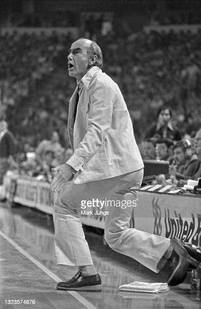 Portland Trail Blazers head coach Jack Ramsey rises from a kneeling position to shout at someone on the court during an NBA basketball game at...