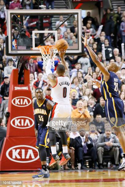 Portland Trail Blazers point guard Damian Lillard takes a jumpshot over Indiana Pacers power forward David West during the Portland Trail Blazers...