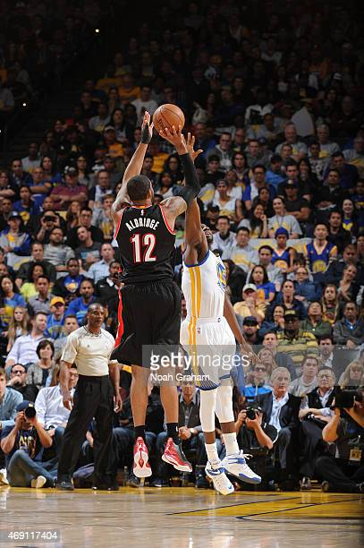 Portland Trail Blazers shoots against Draymond Green of the Golden State Warriors on April 9 2015 at Oracle Arena in Oakland California NOTE TO USER...