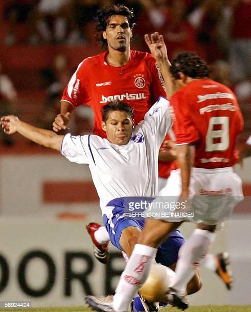 Jorge Britez del Nacional de Uruguay disputa la pelota con Perdigao y Fernandao del equipo brasileno Internacional en partido de Copa Libertadores...