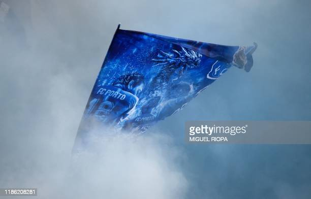 Porto fans wave a flag in the smoke before the start of the Portuguese league football match between FC Porto and FC Pacos de Ferreira at the Dragao...