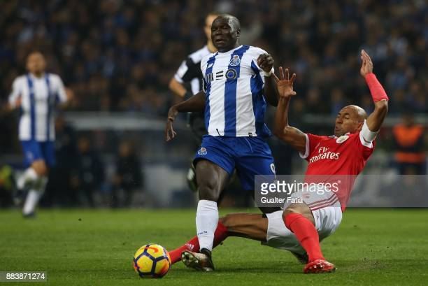 Porto forward Vincent Aboubakar from Camaroes tackled by SL Benfica defender Luisao from Brazil during the Primeira Liga match between FC Porto and...