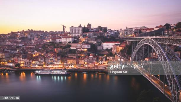 Porto urban skyline at dusk along Douro River with Dom Luis I bridge, Portugal