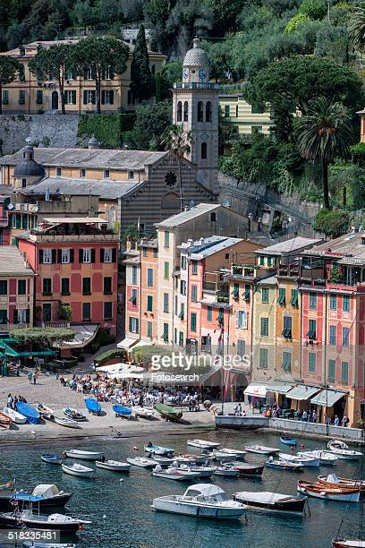 Portofino harbor with fishing boats, brightly colored apartment buildings, outdoor cafes, church and bell tower beyond in lush greenery, Liguria, Italy