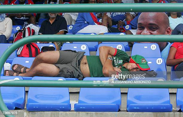 A Bangladesh cricket fan sleeps in the stands next to a cardboard cutout of Bermudan cricketer Dwayne Leverock as rain interrupts play at the Queen's...