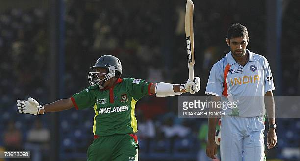 Bangladeshi Cricketer Mushfiqur Rahim celebrates his team's victory over India as Indian Cricketer Munaf Patel looks on following their group stage...