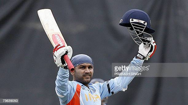 India Cricketer Virendra Sehwag raises his bat after his century during the group stage match between India and Bermuda at the Queen's Park Oval...