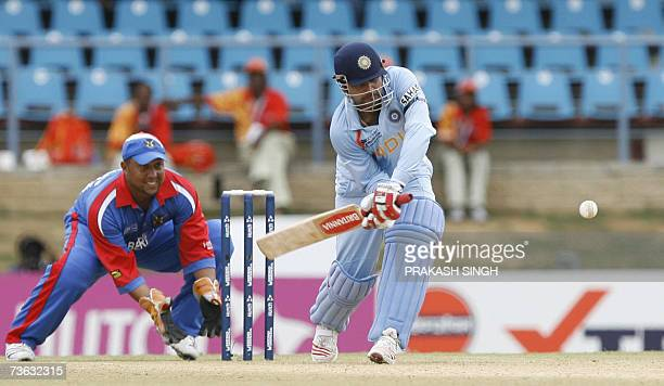 India Cricketer Virendra Sehwag plays as shot as Bernuda Wicket Keeper Dean Minors looks on during group stage match between India and Bermuda at the...