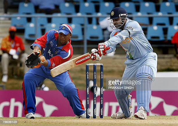 India cricketer Virendra Sehwag plays a shot as Bermuda wicketkeeper Dean Minors looks on during their World Cup Group B match at the Queen's Park...