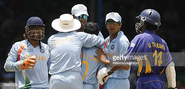 Sri Lankan Cricketer Upul Tharanga walks back to the pavillion as Indian Cricket Captain Rahul Dravid celebrate his wicket with team members at the...