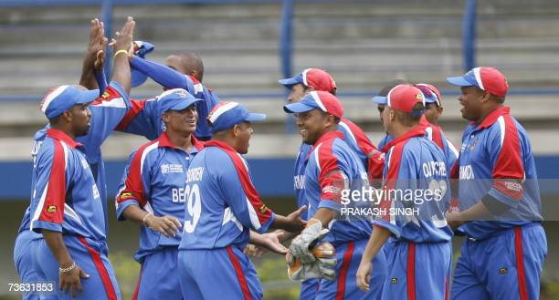 The Bermuda Cricket team celebrates the wicket of India Cricketer Robin Uthappa during group stage match betwen India and Bermuda at the Queen's Park...