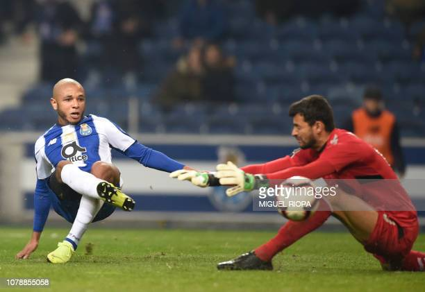 Porto's Algerian forward Yacine Brahimi scores a goal to Nacional's Brazilian goalkeeper Daniel Guimaraes during the Portuguese League football match...