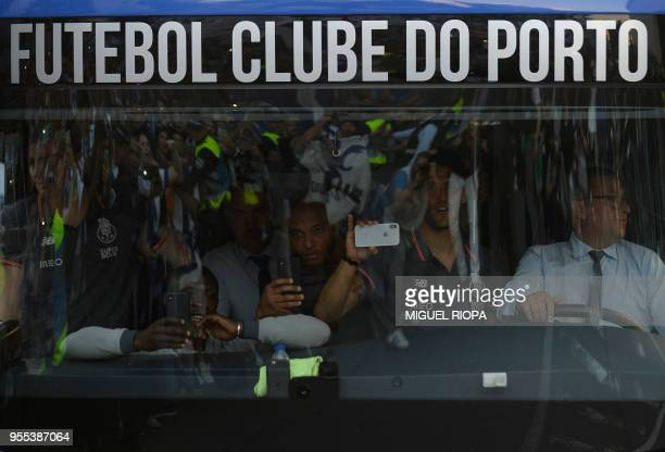 Porto's Algerian forward Yacine Brahimi takes pictures of Porto's supporters greeting the team bus outside the Dragao stadium in Porto ahead of the...