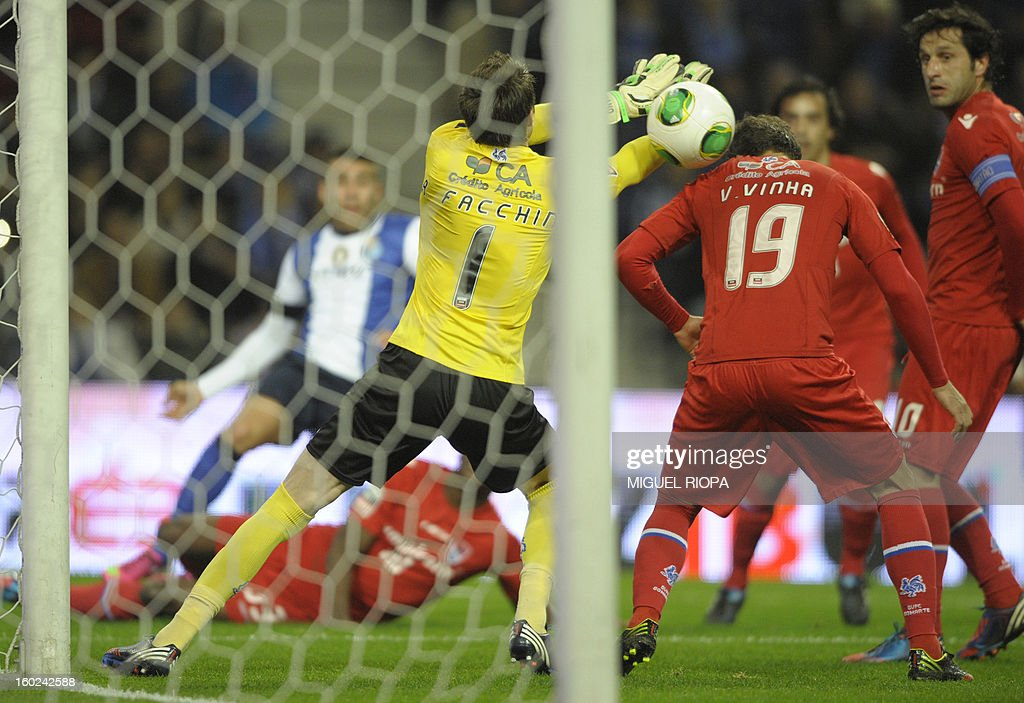 Porto's Argentinian defender Nicolas Otamendi (L) shoots past Gil Vicente's Brazilian goalkeeper Adriano Facchini (C) and defender Vitor Vinha during the Portuguese league football match FC Porto vs Gil Vicente at the Dragao Stadium in Porto on January 28, 2013.