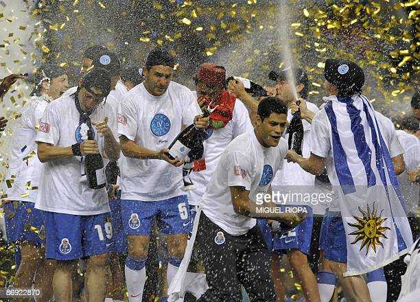 Porto's Argentinians Ernesto Farias, Nelson Benitez and Brazilian Givanilno 'Hulk' Souza celebrate their victory with champagne after their...