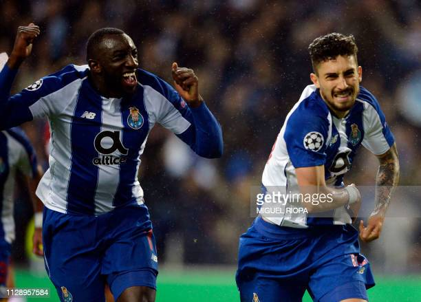 TOPSHOT Porto's Brazilian defender Alex Telles celebrates a goal with teammate Malian forward Moussa Marega during the UEFA Champions League round of...