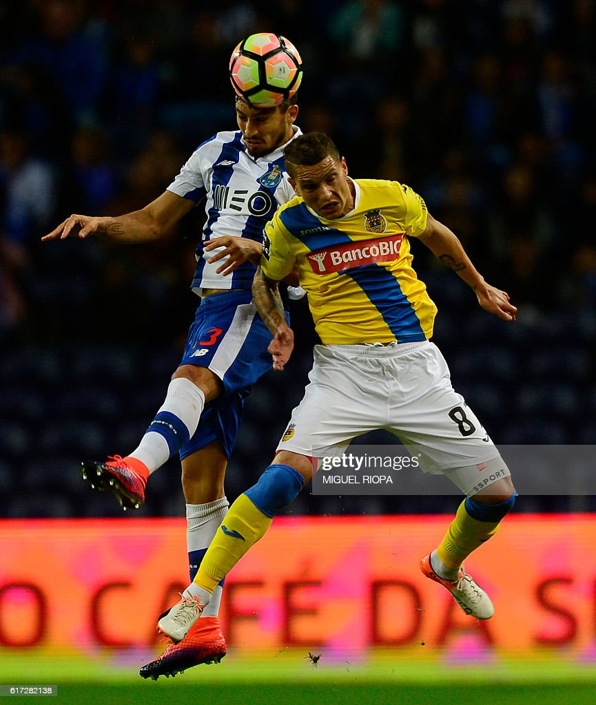 Porto's Brazilian defender Alex Telles (L) jumps for the ball with Arouca's forward Zequinha during the Portuguese league football match between FC Porto and FC Arouca at the Dragao stadium in Porto on October 22, 2016. / AFP / MIGUEL