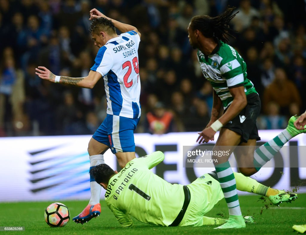 Porto's Brazilian forward Soares (L) vies with Sporting's goalkeeper Rui Patricio before scoring a goal during the Portuguese league football match FC Porto vs Sporting CP at the Dragao stadium in Porto on February 4, 2017. / AFP / MIGUEL
