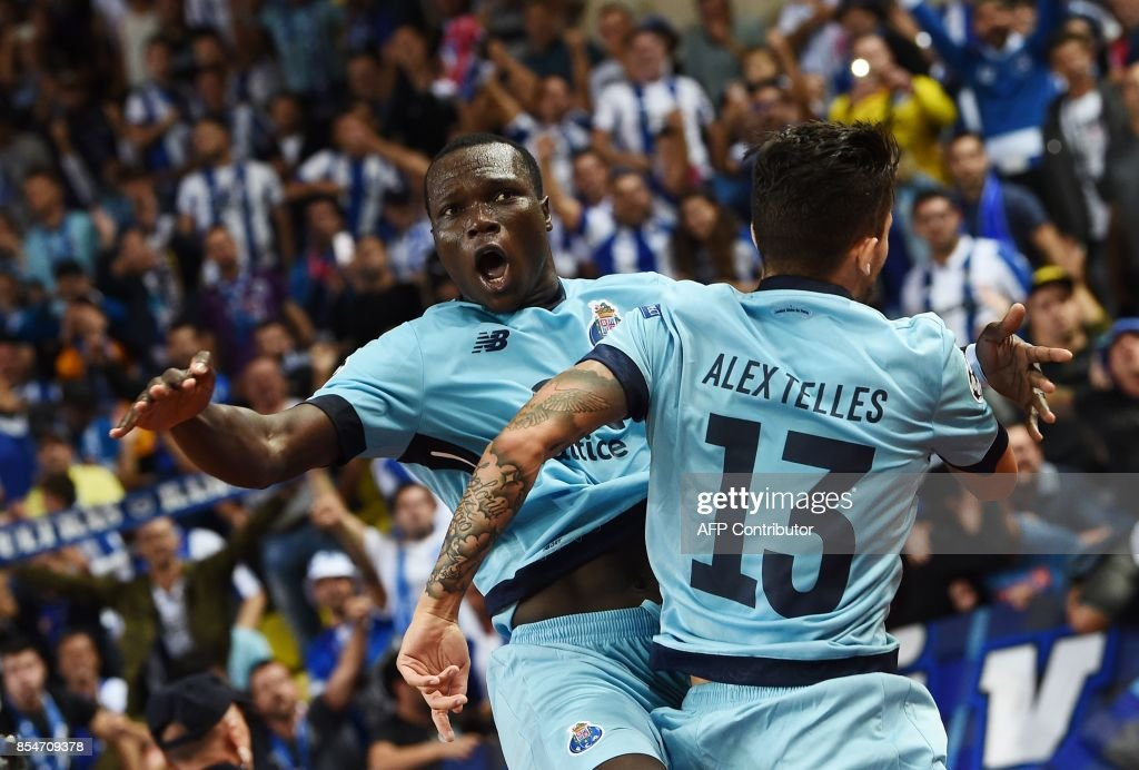 Porto's Cameroonian forward Aboubakar (L) celebrates after scoring a goal with Porto's Brazilian defender Alex Telles during the UEFA Champions League Group G football match AS Monaco FC vs FC Porto on September 26, 2017 at the Louis II stadium in Monaco. / AFP PHOTO / Anne-Christine POUJOULAT