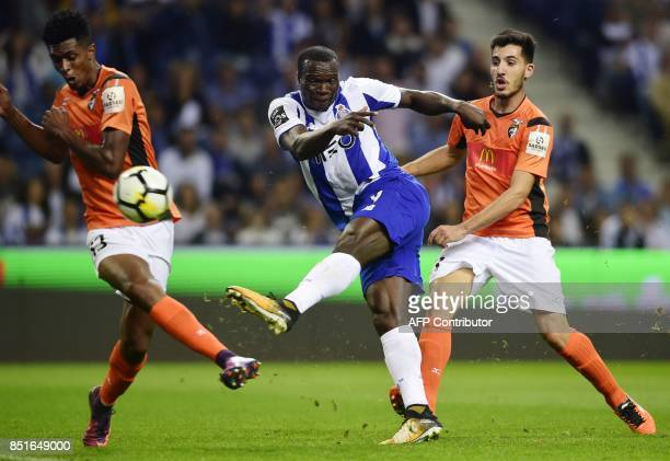Porto's Cameroonian forward Vincent Aboubakar kicks the ball between Portimonense's Brazilian defender Felipe Macedo and midfielder Pedro Sa to score...