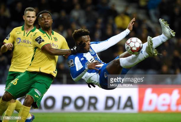 Porto's Cape Verdean forward Ze Luis kicks the ball to score a goal beside Pacos Ferreira's Brazilian defender Maracas during the Portuguese league...