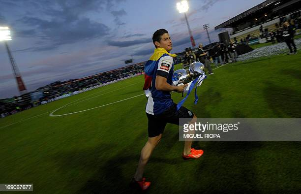 Porto's Colombian forward James Rodriguez runs with the trophy after winning the Portuguese league at the end of the football match against Pacos...