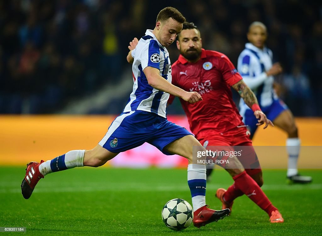 Porto's forward Diogo Jota (L) kicks the ball beside Leicester City's Polish defender Marcin Wasilewski to score his team's fifth goal during the UEFA Champions League football match FC Porto vs Leicester City FC at the Dragao stadium in Porto on December 7, 2016. / AFP / MIGUEL