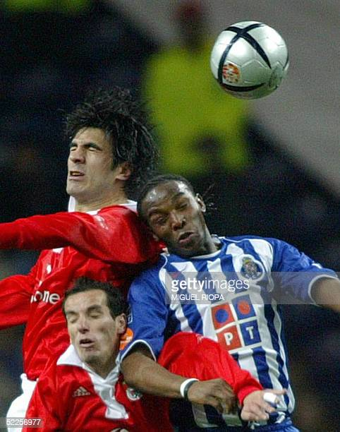 Porto's forward South African Benny McCarthy jumps for the ball with Benfica's Brazilian Petit and Ricardo Rocha in the Portuguese Superleague...